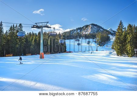 People skiing down the ski at the top point of Hausberg ski lift in bavarian Alps