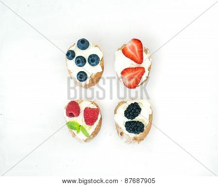 Set Of Small Sweet Sandwiches With Cream-cheese And Fresh Forest Berries Over A White Background Wit