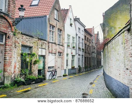 Medieval Empty Side Street Of Bruges, Belgium, With A Bike Parked At One Side