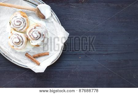 Cinnamon Rolls With Cream-cheese Icing And Cinnamon Sticks On A Silver Dish Over A Dark Wooden Desk
