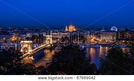 The Night View Of The Chain Bridge, Saint Istvan's Basilica And The Danube In Budapest From The Buda