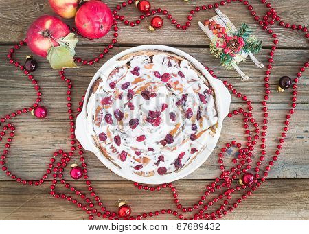 Apple, Cranberry And Cinnamon Roll Cake With Creamy Icing And Christmas Decoration Over A Rustic Woo