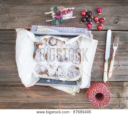 Cinnamon Buns With Cream-cheese Icing In A Baking Dish With Christmas Decorations Over A Rustic Wood