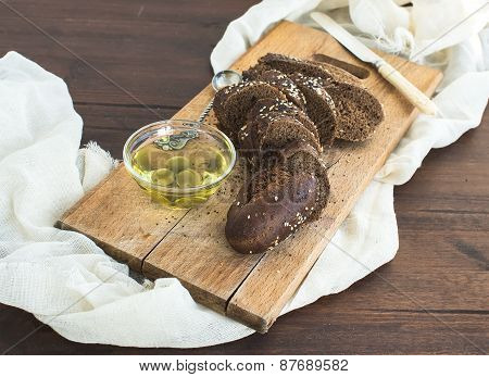 Dark Baguette Cut In Slices With Olive Oil On A Rustic Wooden Board Over A Piece Of White Linen Fabr