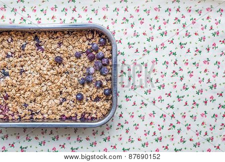 Oat Granola With Fresh Berries In A Silver Baking Dish Over A Flower Patterned Table Cloth