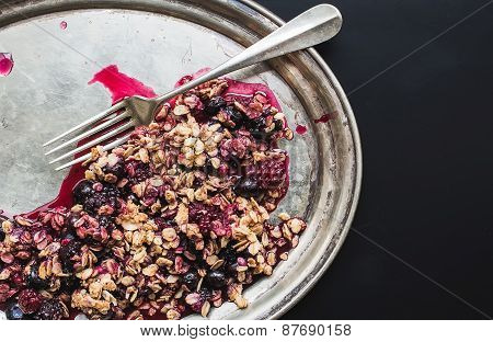 Oat Granola With Fresh Berries On A Silver Dish With A Fork On Black