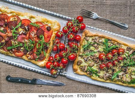 Two Square Pizzas With Fresh Arugula And Cherry-tomatoes On Silver Trays Over A Sackcloth Background