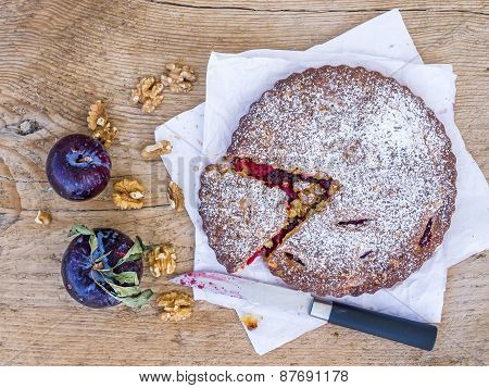 Plum Cake With Walnuts And Fresh Ripe Plums On White Paper Over A Wooden Background