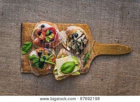 Antipasti Brusquetta Set On A Rustic Wooden Board Over A Sackcloth Surface
