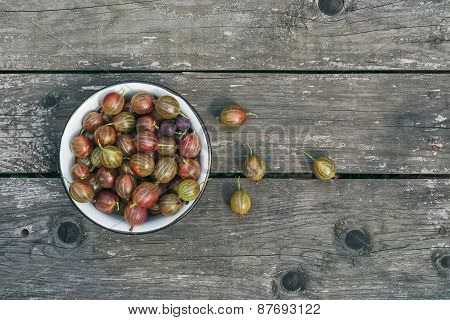 A Bowl Of Gooseberries On A Wooden Surface