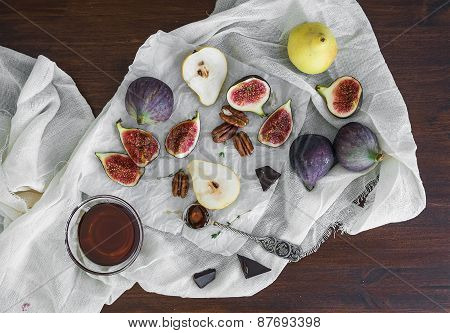 Fresh Figs, Chocolate, Pears And Pekan Nuts With Honey On A Wooden Board