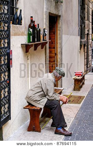 Old Man With Hat And Cane Sitting In Front Of A Wine Shop
