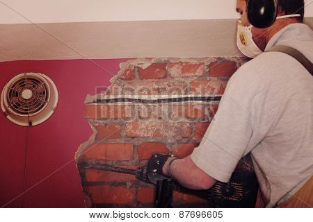 Adult repairman demolish wall in room.