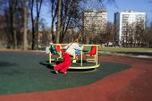 foto of playground  - Cute little girl playing on child playground spring sunny day - JPG
