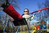 image of seesaw  - Cute little girl swinging on seesaw on children playground - JPG