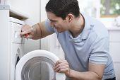 foto of washing machine  - Engineer Mending Domestic Washing Machine In Kitchen  - JPG