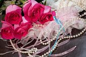 picture of garter  - Beautiful pink roses pearl beads and white stockings with garter lying on a table - JPG