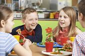 image of school lunch  - Group Of Pupils Sitting At Table In School Cafeteria Eating Lunch - JPG