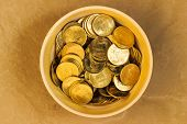 stock photo of indian currency  - Indian coins saved in a bowl on a plain background - JPG