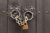 stock photo of wooden door  - Old rusty metal lock on a wooden door  - JPG