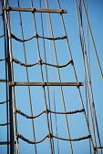 stock photo of  rig  - rigging ropes at the old sailing vessel against blue sky - JPG
