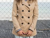 stock photo of coat  - Slender girl in a beige coat with buttons on the coat - JPG