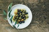 picture of olive branch  - A plate of Mediterranean olives in olive oil with a branch of olive tree over a rough old wooden desk with a copy space - JPG