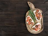picture of tomato sandwich  - Sandwiches or brushtta with roasted cherry tomatoes soft cheese garlic and herbs on a rustic wooden board over a dark wood background with a copy space - JPG