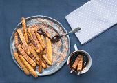 picture of churros  - Churros with chocolate sauce on a metal plate over a linen table cloth - JPG