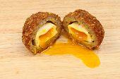 foto of yolk  - Runny yolk scotch egg cut in half on a wooden board - JPG