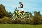 pic of levitation  - The girl on a bicycle in the park levitates over the meadow - JPG
