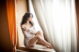 foto of foot  - Attractive sexy girl in white dress posing provocatively in window frame - JPG