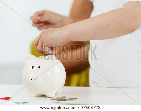 Child Hand Putting Pin Money Coins Into White Piggybank Slot
