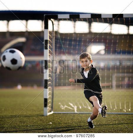 boy plays football on stadium