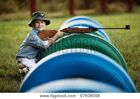 little boy with airgun outdoors