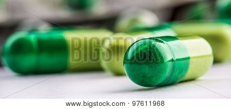 Pills. Tablets. Capsule. Heap of pills. Medical background. Close-up of pile of yellow green tablets
