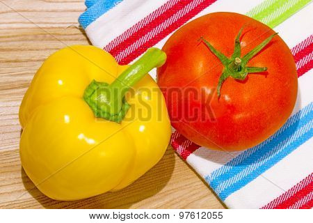 Red Tomato And Yellow Bell Pepper On Wood Slicing Board