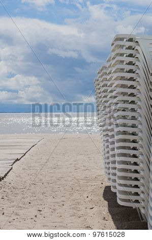 Sunbeds Stacked On The Beach During Stormy Weather