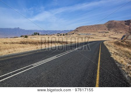 Straight Asphalt Road Bordered With Dry Grass