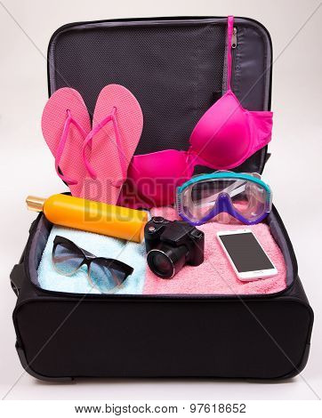 Preparation For Trip Concept - Open Suitcase Full Of Travel Items