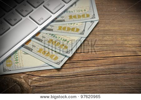 Computer Keyboard  And Dollar Cash On The Wood Background