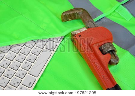 Keyboard In The Green Reflective Safety Vest And Wrench