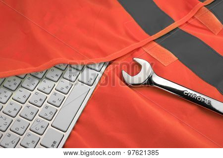 Keyboard In The Red Reflective Safety Vest And Wrench