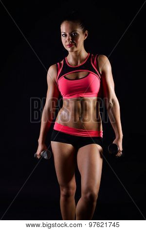 Portrait of young fitness woman posing with dumb-bells. Muscular female body with sweat. Perfect sportive female body. Sporty girl over black background.