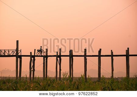 A woman ride bycycle on U-Bein bridge