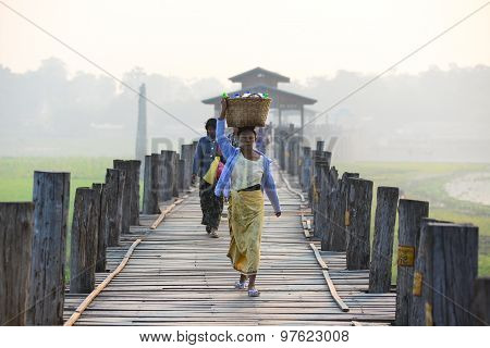Unidentified people walk on U-Bein bridge