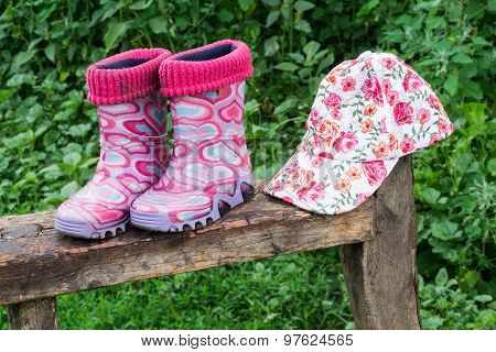 Children Rubber Boots And A Cap On The Bench