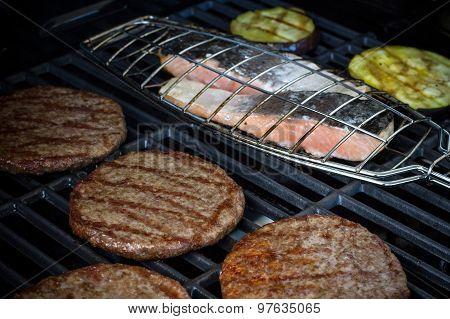 Hamburger Slices, Salmon Steak And Eggplant On Grill Rack