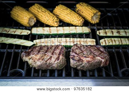 Rib Eye Steak With Zucchini And Corn On Gas Grill