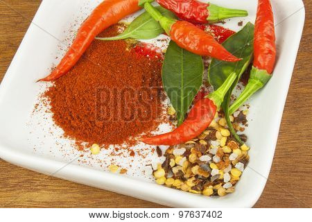 Spices in a ceramic bowl. Freshly picked chili peppers on a wooden table.